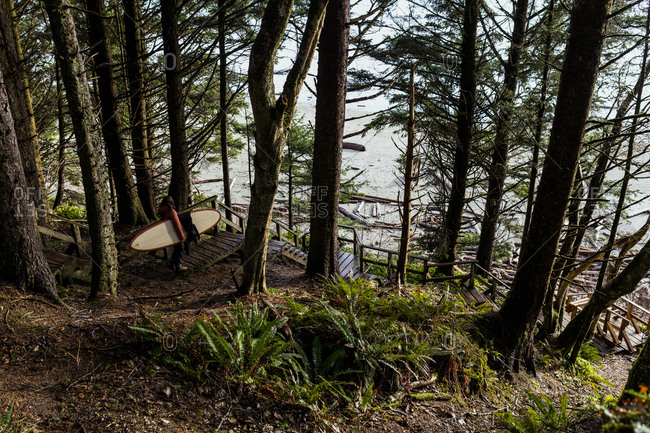 Female surfer walking in forest in the Pacific Northwest