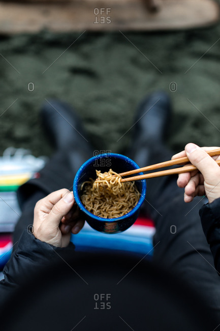 Eating instant noodles on the beach with chopsticks