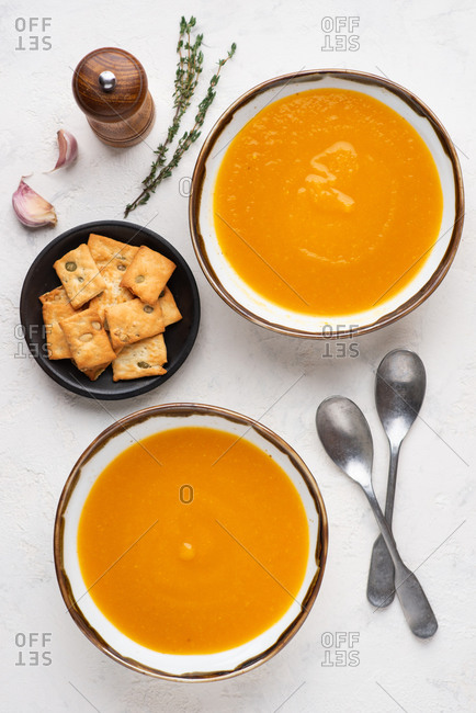 Overhead view of two bowls of pumpkin soup served with cheese biscuits with pumpkin seeds