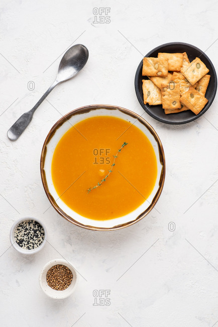 Overhead view of bowl of pumpkin soup served with cheese biscuits with pumpkin seeds