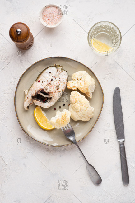 Cod fish roasted with cauliflower served on plate with lemon over white background