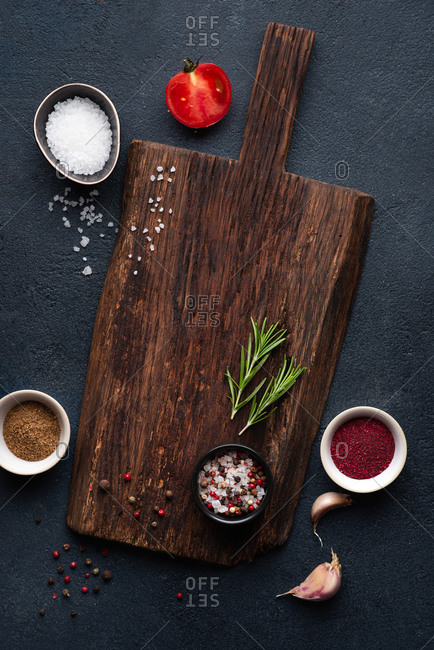 Empty cutting board and spices over dark background