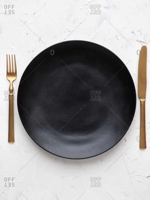 Overhead view of empty black ceramic plate with gold fork and knife by sides