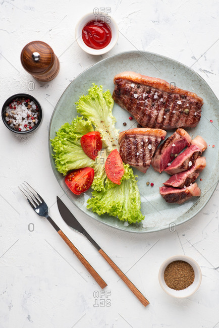 Top view of grilled beef black angus steak served with leaf salad and tomatoes on the plate