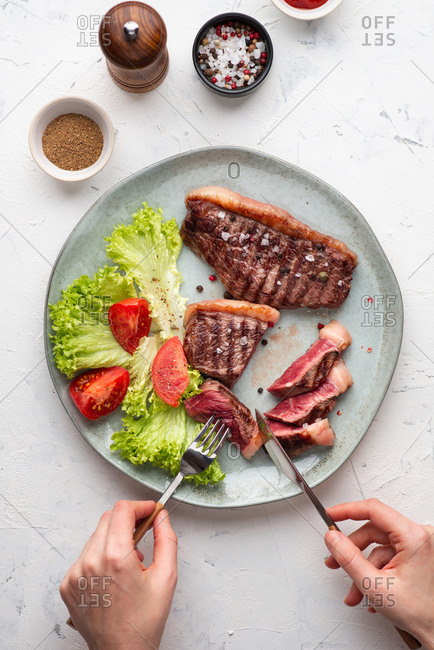 Top view of grilled beef black angus steak served with leaf salad. Person cutting a piece of steak