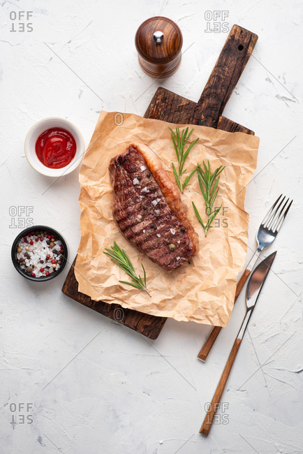 Top view of grilled beef black angus steak served on dark wooden chopping board