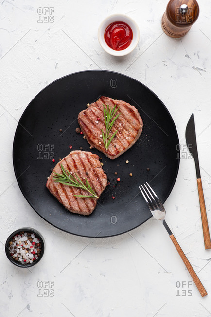 Top view of grilled beef steak served on black ceramic plate
