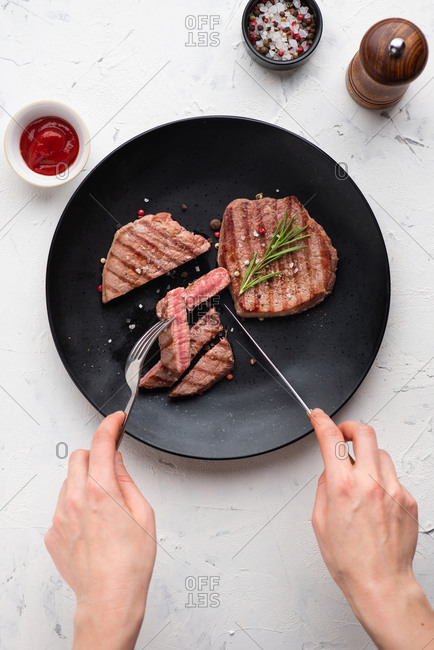 Top view of grilled beef steak served on black ceramic plate. Person cutting a piece of steak