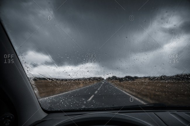 Country road and storm clouds seen from car