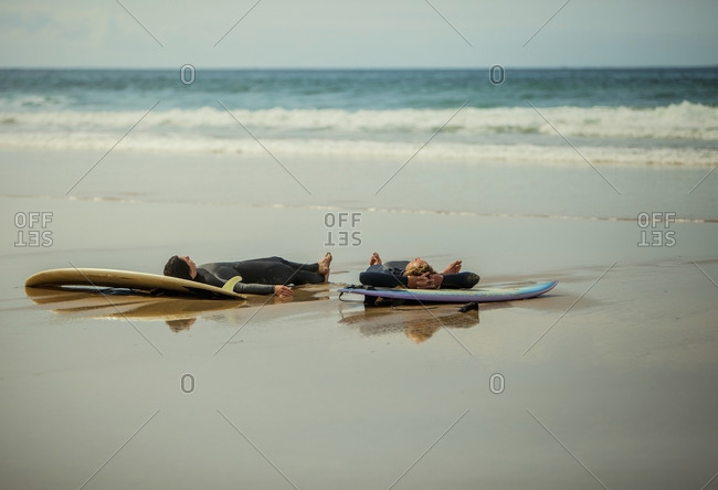 Male friends lying down on surfboards at beach