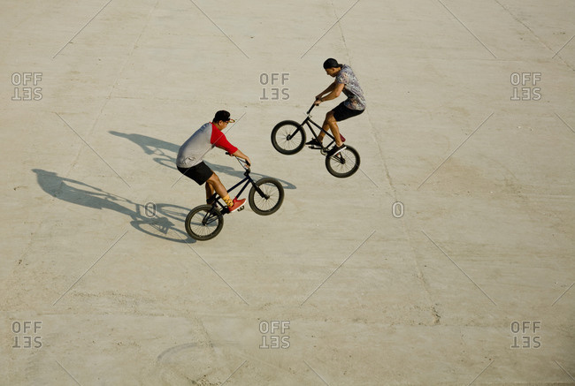 Young men doing wheelie stunts on footpath during sunny day