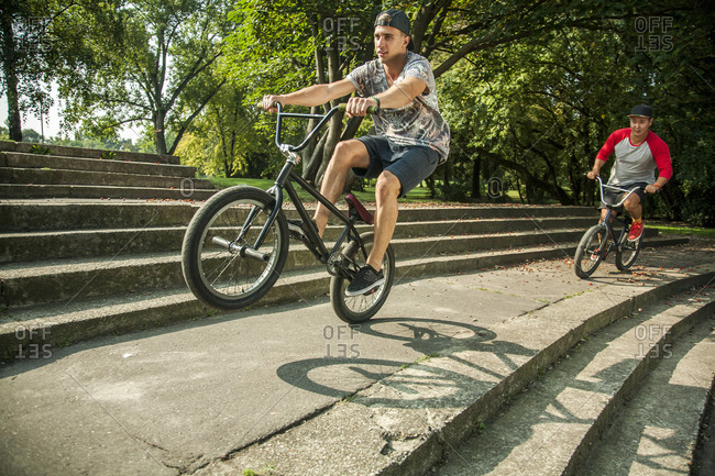 Young man doing wheelie stunt with BMX bicycle against friend cycling on steps at public park