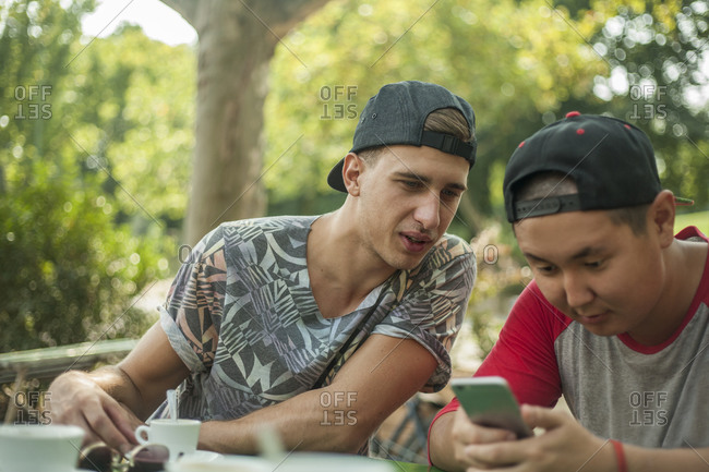 Young man peeking into smart phone of friend at cafe