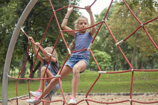Girls climbing on jungle gym at playground
