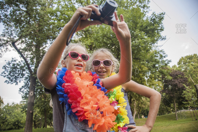 Cheerful girls in sunglasses and floral garlands using camera at park