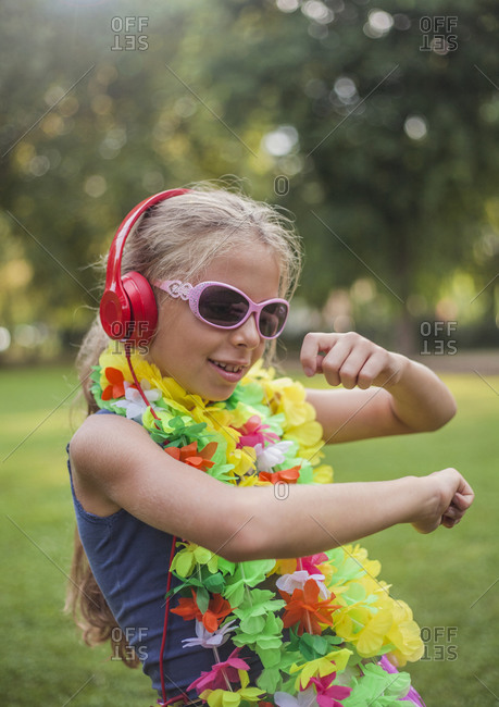 Cute girl in floral garland dancing while listening music through headphones at park