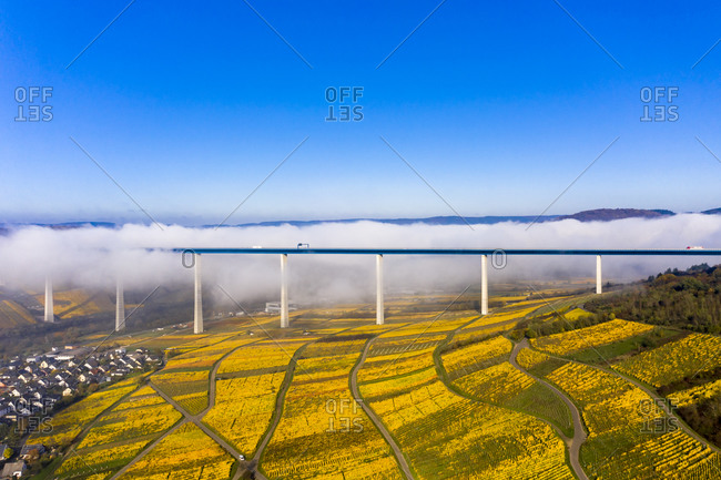 Germany- Rhineland-Palatinate-Zeltingen-Rachtig- Town and vineyards with viaduct in autumn- aerial view