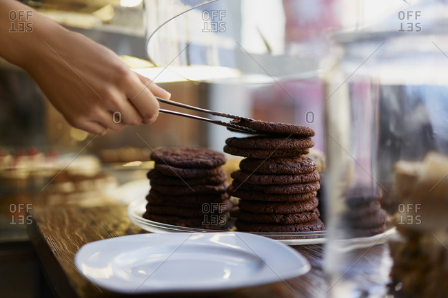 Hand of barista removing cookie biscuits while working at cafe