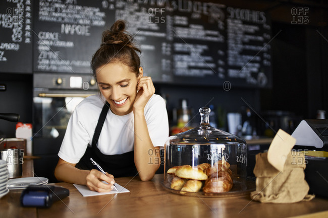 Smiling barista writing in note pad while working at cafe