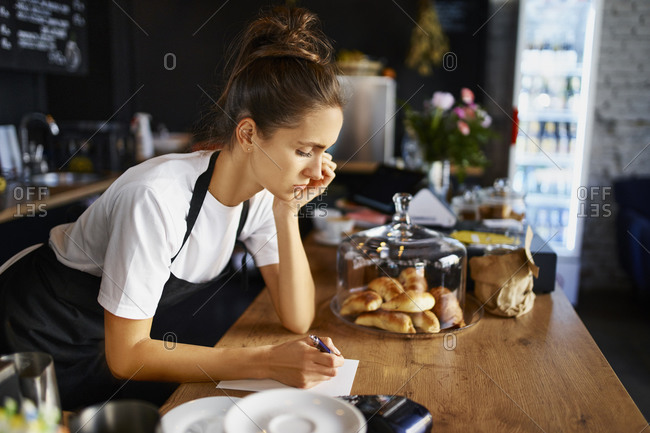 Contemplating female waitress writing in note pad while working at coffee shop