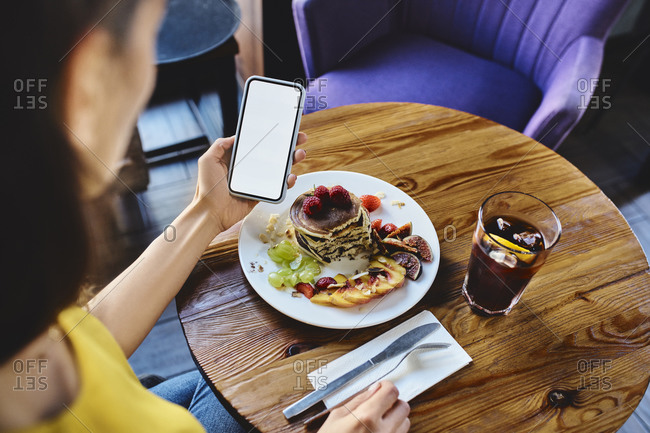 High angle view of young female with pancake using smart phone at table in cafe
