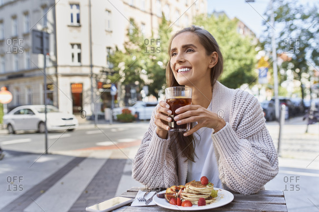 Smiling young female with pancake drinking while sitting at table in city