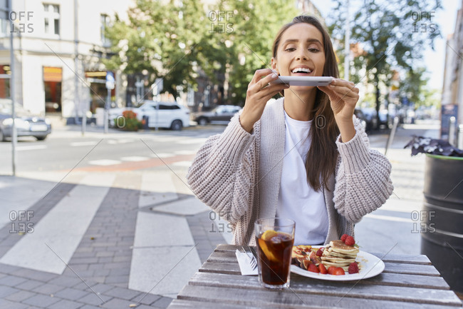 Woman taking photo of food and drink on table while sitting at sidewalk at cafe