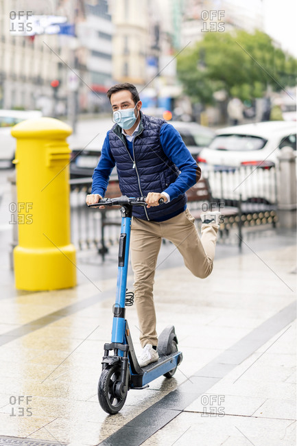 Young man wearing protective face mask riding electric scooter on footpath in city during COVID-19