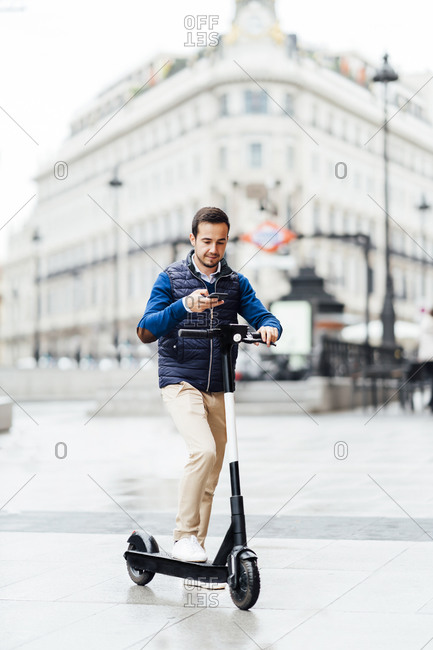 Young man doing contactless payment of electric scooter while standing on footpath in city