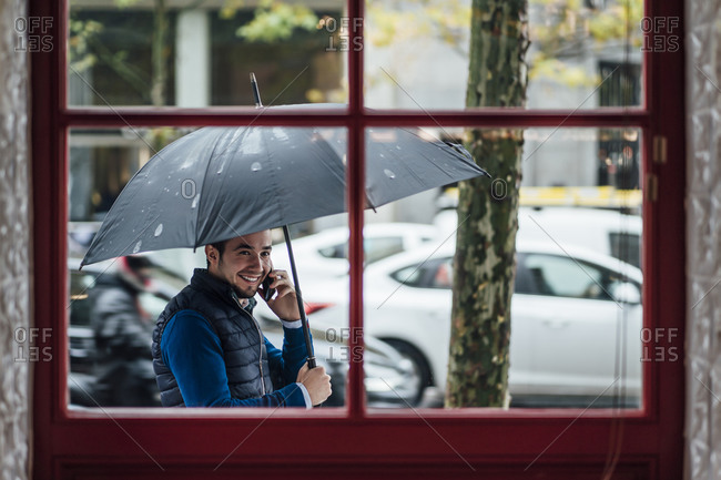 Happy man with umbrella talking on smart phone while looking at window during rainy season