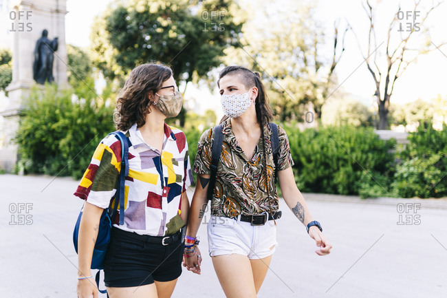 Young lesbian couple looking at each other while walking on street during COVID-19 crisis