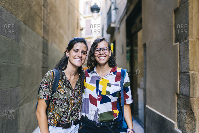 Happy lesbian couple smiling while standing on alley amidst building in city