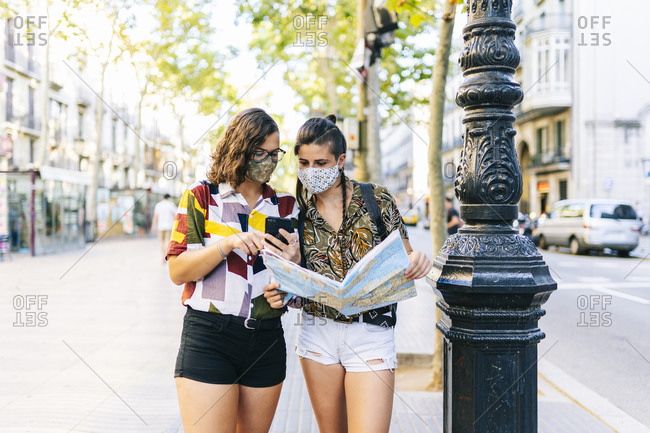 Homosexual couple looking at map and using smart phone while standing on street in city