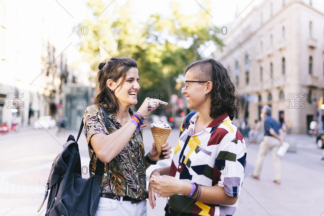 Lesbian daubing ice cream on girlfriend's nose while standing in city