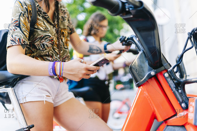 Homosexual couple using smart phone to unlock the electric bicycle