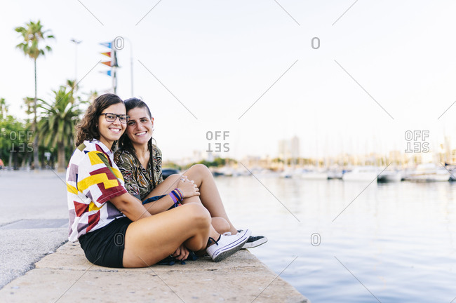 Smiling young girlfriends sitting on promenade at harbor