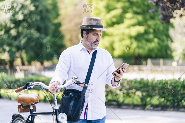 Mature man using mobile phone while standing with bicycle in public park