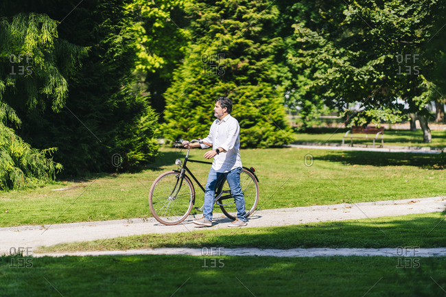 Mature man looking away while walking with bicycle in public park