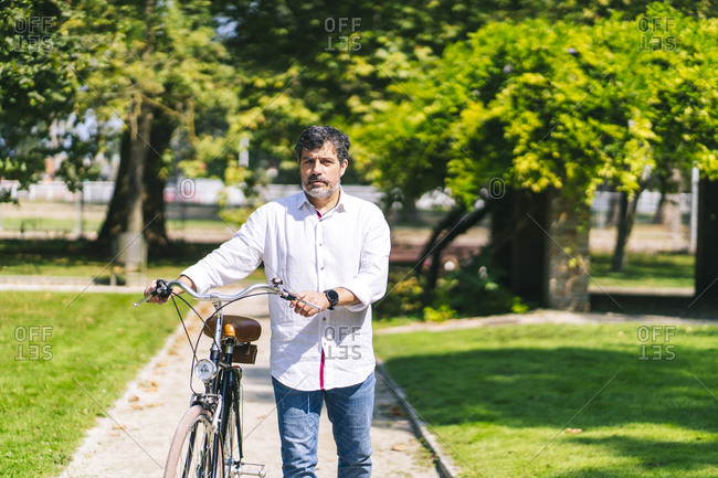 Mature man with bicycle walking on walkway in park on sunny day