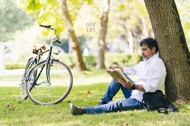 Mature man reading book while leaning on tree trunk at public park