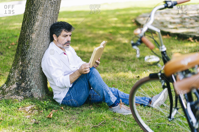 Mature man reading book with concentration while sitting in public park