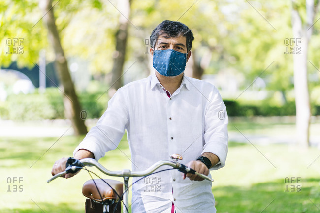 Mature man with protective face mask with bicycle at public park during COVID-19