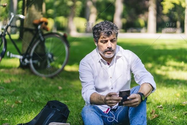 Mature man listening music through mobile phone at public park