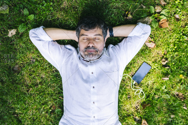 Mature man lying on grass while listening music through mobile phone in park