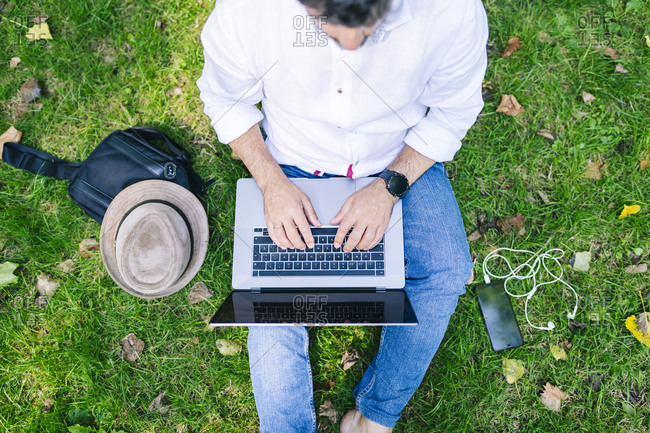 Mature man using laptop while sitting on grass field at public park