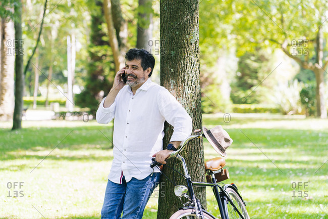 Happy mature man talking on smart phone while leaning on tree at public park