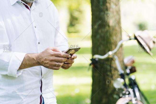 Mature man using mobile phone at public park