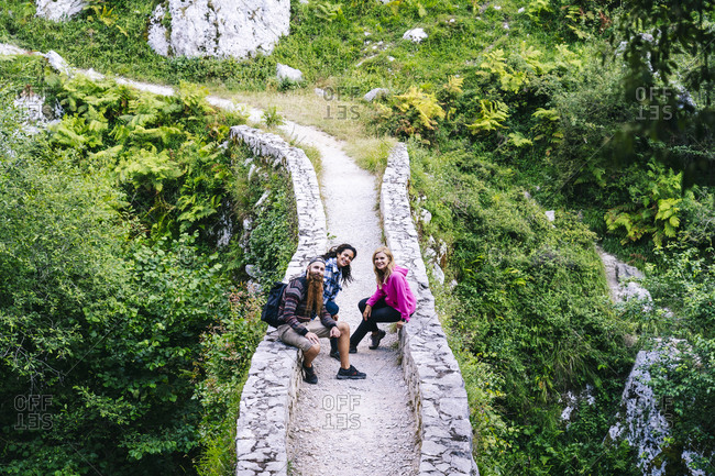 Friends sitting on walkway while hiking in Picos De Europa mountain- Asturias- Spain