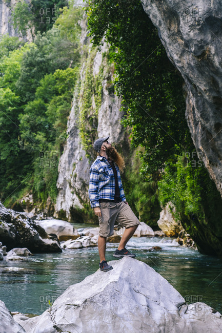 Young man standing on rock over river while hiking in Picos De Europa mountain- Asturias- Spain