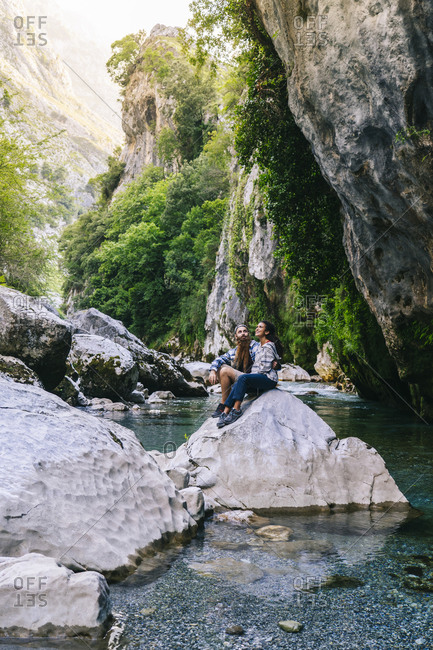 Young couple sitting on rock while hiking in Picos De Europa mountain- Asturias- Spain